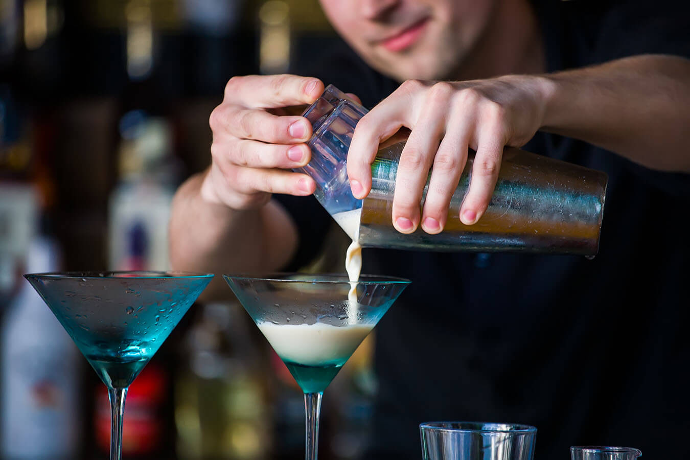 The bartender mixes a summer cocktail at the bar